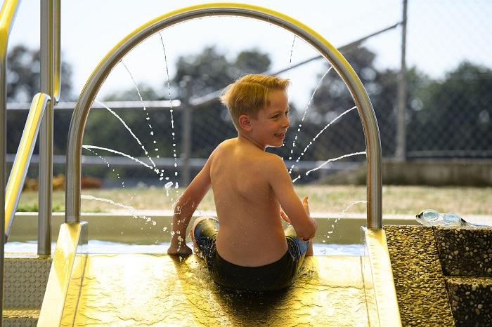 Gartenhallenbad Kinderaußenbecken Kind auf Rutsche